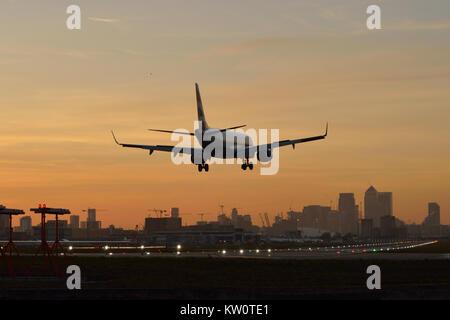 British Airways BA CityFlyer Embraer landing at London City Airport at dusk - Stock Photo
