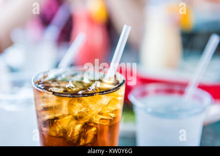 Macro closeup of iced tea or soda with ice cubes and straw in glass - Stock Photo