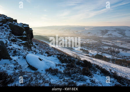 Dawn at Bamford edge in the Peak District on a cold winter morning. An old abandoned millstone covered in snow. - Stock Photo