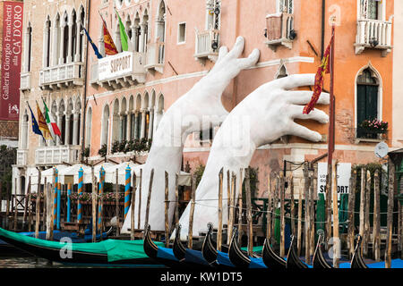 Giant Hands of Venice's Grand Canal, a sculpture called Support by artist Lorenzo Quinn, symbolizing the threat - Stock Photo