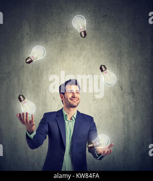 Businessman juggling with burning light bulbs having plenty of great ideas. - Stock Photo