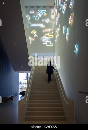 A young woman walks up stairs featuring a neon light installation named Lucky Charms by artist Pae White at the - Stock Photo