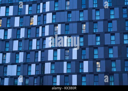 Close up of a building showing identical windows, with blue and grey toned cladding - Stock Photo