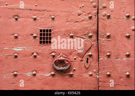 Closeup view of an old red door of medieval style with metallic rivets, heart shaped keyhole plate, cast iron knocker - Stock Photo