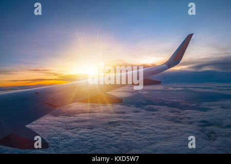 Amazing sunrise view from the window seat on airplane. - Stock Photo