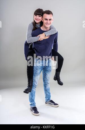 Teenage boy giving his girlfriend a piggyback ride - Stock Photo