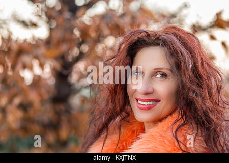 Closeup of a smiling mature woman with slight strabismus of Venus wearing orange fur collar and showing wrinkles, - Stock Photo