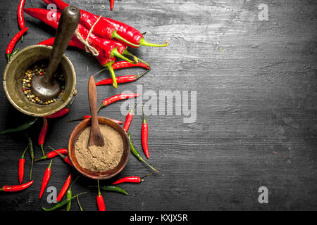 Grain of hot pepper in a mortar with a pestle. On the black chalkboard. - Stock Photo