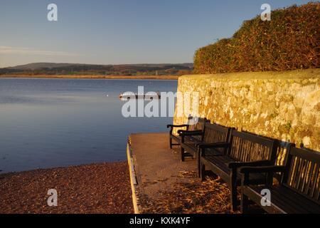 Wooden Benches on The Goat Walk, Topsham, Exe Estuary in the Golden Light of Dawn. Devon, UK. January, 2018. - Stock Photo