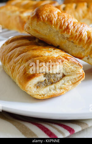 Freshly baked pork sausage rolls made with puff pastry fresh out of the oven - Stock Photo