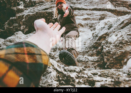 Couple Man and Woman help giving hands climbing rocky mountains Love and Travel Lifestyle concept hiking adventure - Stock Photo