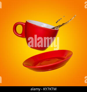 Creative surreal design with a red coffee cup and saucer on a yellow background. A cup and saucer flying in the - Stock Photo