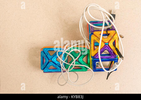 Toy house surrounded by technology, wires - Stock Photo