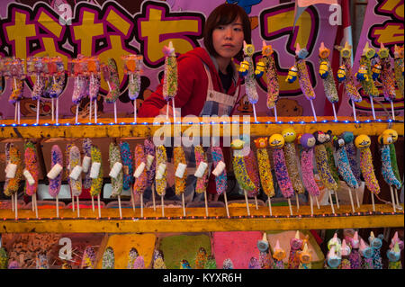 31.12.2017, Tokyo, Japan, Asia - A young woman sells multicoloured chocolate bananas at a roadside stall in Harajuku. - Stock Photo