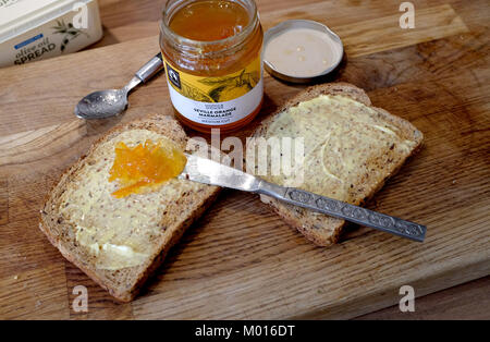Wholemeal brown toast with M&S Seville Orange Marmalade - Stock Photo