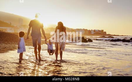 Joyful family having fun on a beach, summer portrait - Stock Photo