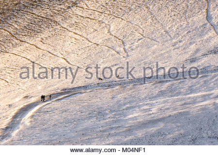 Three people and two dogs walking on a path covered by snow on Monte Cucco (Umbria, Italy) during golden hour - Stock Photo