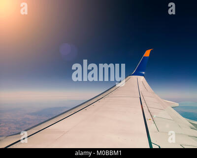 airplane wing seen during air travel in the sky - Stock Photo