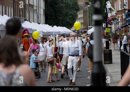 Crowd scene at the Marlyebone Summer Fayre Marlyebone Food Festival in London on a sunny day with yellow balloons - Stock Photo