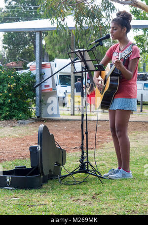 A female busker singing and playing an acoustic guitar at the outdoor markets in Margaret River, WA, Australia. - Stock Photo