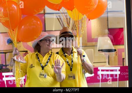 Two volunteers smiling in yellow shirts holding orange balloons at the Marlyebone Summer Fayre Marlyebone Food Festival - Stock Photo