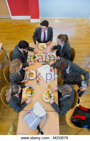 School children having lunch in school canteen - Stock Photo
