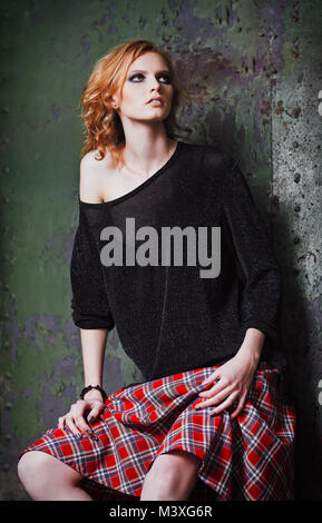 Grunge fashion: portrait of a beautiful young redhead girl (informal model) in plaid skirt and blouse - Stock Photo