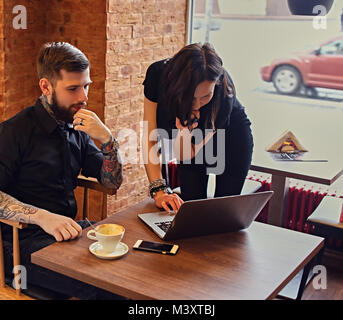 A man with tattooed arms and brunette female using a laptop in a - Stock Photo