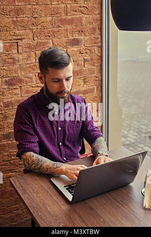 A man with tattooed arms working with a laptop. - Stock Photo