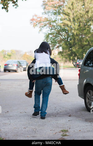 Brother Giving His Sister a Piggyback Ride - Stock Photo