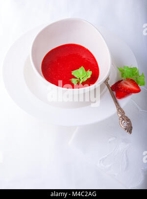 Fresh Strawberry soup with mint on white background - Stock Photo