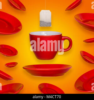 Creative surreal design with a red coffee cup and saucer and tea bag on a yellow background. A cup and saucers flying - Stock Photo