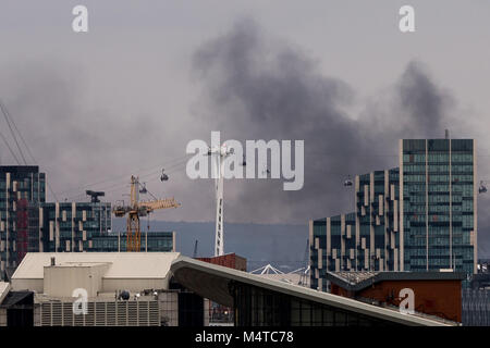 London, UK. 18th Feb, 2018. London Fire: Black smoke rises over buildings from east London with Emirates airline - Stock Photo
