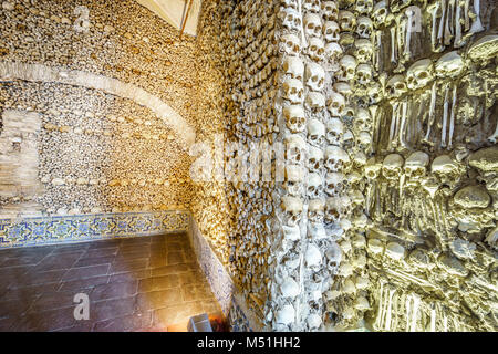 Close-up of skulls on a bone-laid wall with lamp-lit corner in the background, Chapel of Bones in Royal Church of - Stock Photo