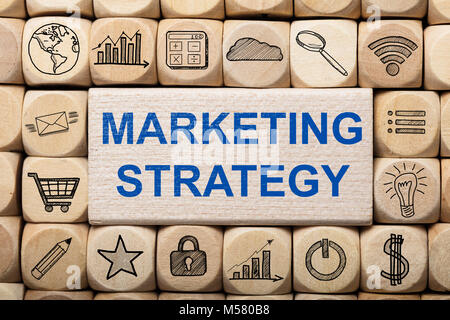 Full frame shot of marketing strategy text on wooden block surrounded by various computer icons - Stock Photo