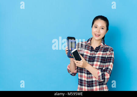 smiling young woman using mobile smartphone with online account paying bill through credit card machine isolated - Stock Photo