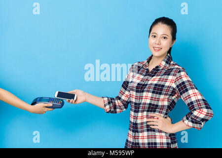 confident smiling woman face to camera standing in blue background and using mobile smartphone paying personal bill - Stock Photo