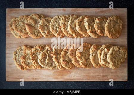 Two rows of freshly cooked plain American cookie biscuits laid out to cool on a wooden board. - Stock Photo