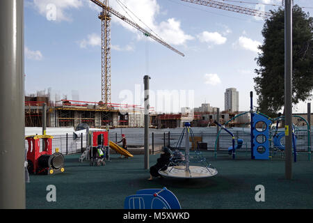Haredi Jewish women with their children in playground next to a construction site at the former German Protestant - Stock Photo
