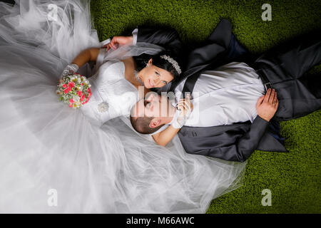 Smiling bride and groom are lying on the grass  -like carpet. - Stock Photo