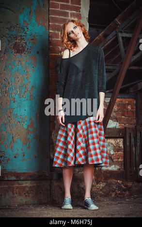 Grunge fashion: portrait of a beautiful young redhead girl in plaid skirt and sweater - Stock Photo