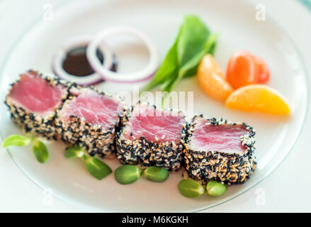 Seared tuna with sesame seeds with green salad on white plate - Stock Photo