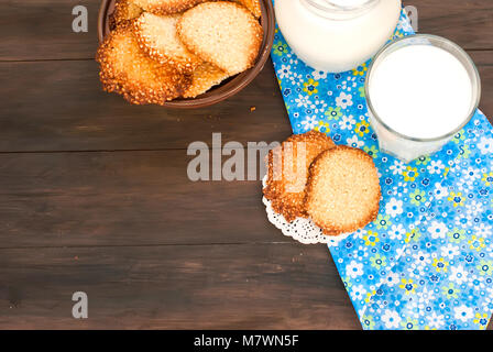 homemade sesame cookies and glass of milk on a dark wooden table - Stock Photo