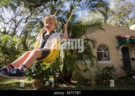 Young boy playing on a swing in yard - Stock Photo