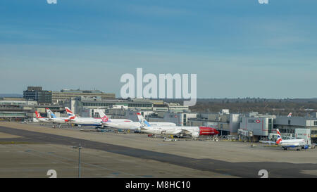 London Gatwick, March 15th, 2018: Airplanes of different airliners on tarmac awaiting passengers at London Gatwick's - Stock Photo