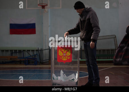 Saint Petersburg, Russia. 18th Mar, 2018. A man casts his ballot paper during the 2018 Russian presidential election - Stock Photo