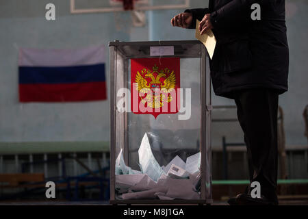 Saint Petersburg, Russia. 18th Mar, 2018. A man casts ballot paper during the 2018 Russian presidential election - Stock Photo