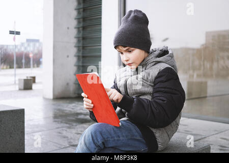 7 year old boy playing online game on tablet computer outdoors in winter - Stock Photo