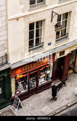 Man walking his dog in front of a creperie at Ile Saint-Louis. Paris, France. - Stock Photo