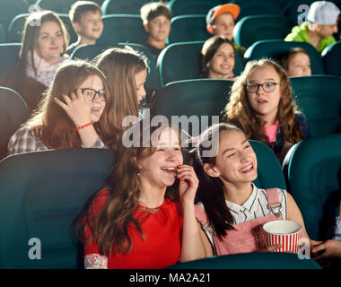 Happy girls laughing by watching interesting movie in the cinema. They smiling, looking satisfied. There are many other emotional children on the background. - Stock Photo